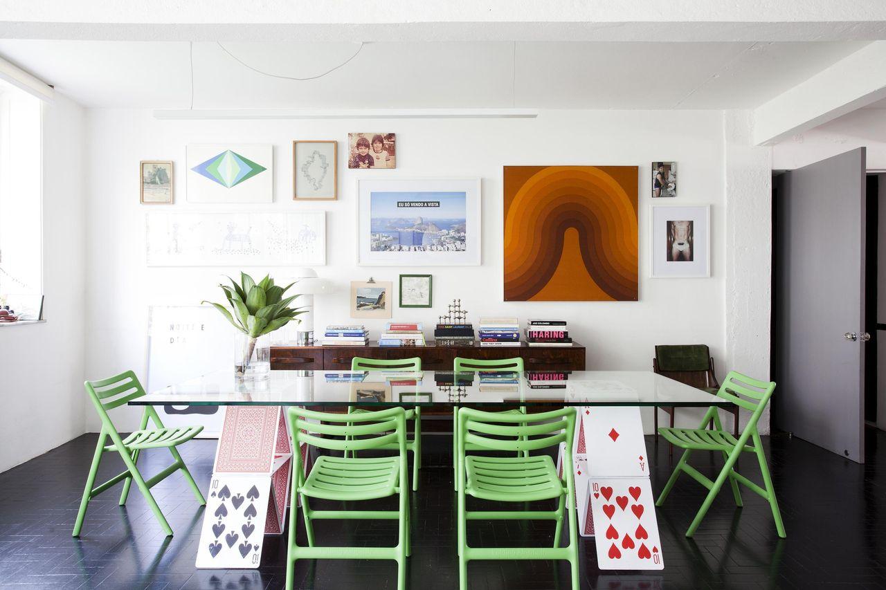 mesa de jantar de vidro com cavaletes estilizados como um castelo de cartas de baralho